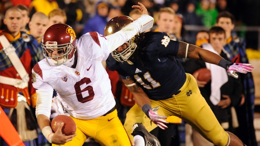Southern California quarterback Cody Kessler heads upfield in front of Notre Dame linebacker Ishaq Williams during the fourth quarter of an NCAA college football game Saturday, Oct. 19, 2013, in South Bend, Ind. (AP Photo/Joe Raymond)