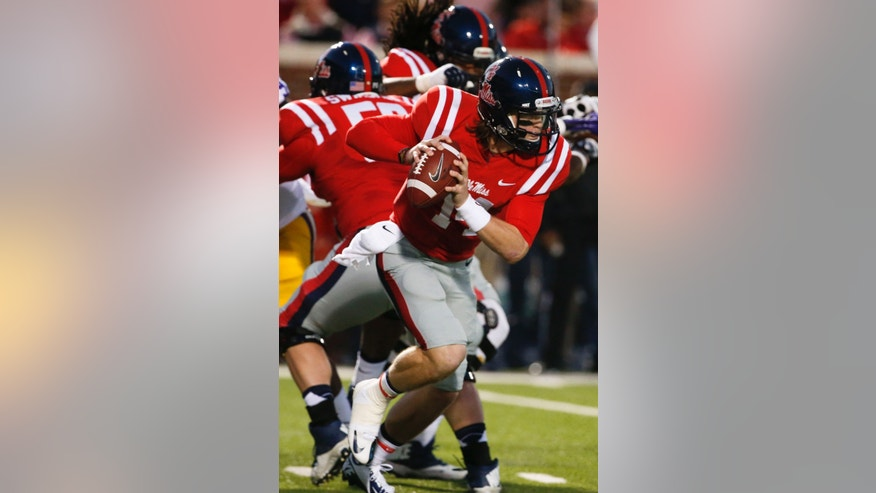 Mississippi quarterback Bo Wallace (14) runs out of the passing pocket for a first down against LSU in the first half of an NCAA college football game in Oxford, Miss., Saturday, Oct. 19, 2013. (AP Photo/Rogelio V. Solis)