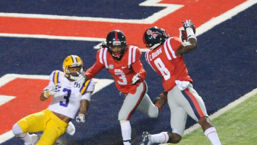 Mississippi defensive back Chief Brown (8) intercepts a pass intended for LSU's Odell Beckham Jr. (3) as Mississippi defensive back Charles Sawyer (3) also defends during an NCAA college football game in Oxford, Miss., Saturday, Oct. 19, 2013. (AP Photo/The Oxford Eagle, Bruce Newman)