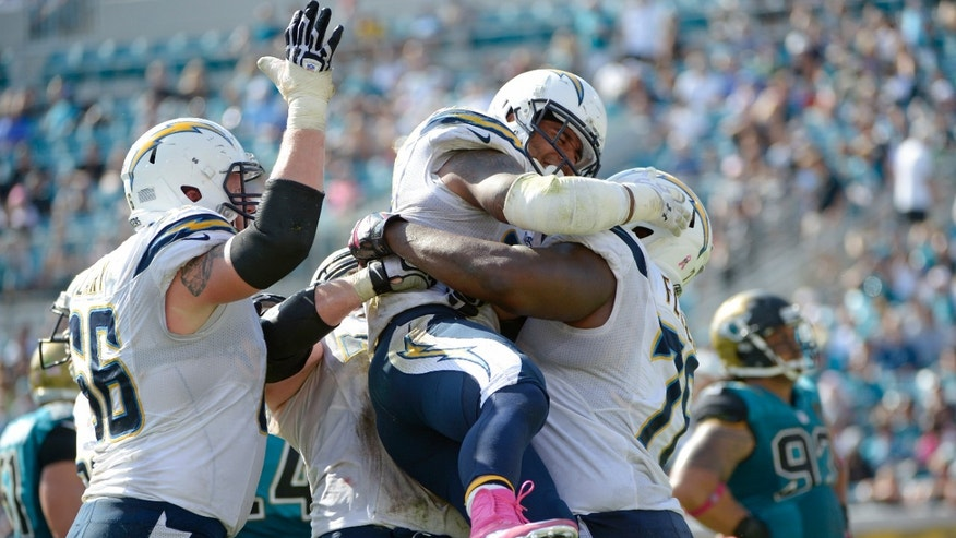 San Diego Chargers running back Ryan Mathews, center, is mobbed by teammates after scoring a touchdown on a 3-yard run against the Jacksonville Jaguars during the second half of an NFL football game in Jacksonville, Fla., Sunday, Oct. 20, 2013.(AP Photo/Phelan M. Ebenhack)