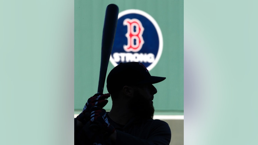 "With a ""B strong"" emblem on the Green Monster wall in honor of the Boston Marathon bombing surviviors, Boston Red Sox's Dustin Pedroia holds a bat during team baseball practice at Fenway Park in Boston, Monday, Oct. 21, 2013. The Red Sox are preparing to face the St. Louis Cardinals in Game 1 of the World Series on Wednesday. (AP Photo/Elise Amendola)"