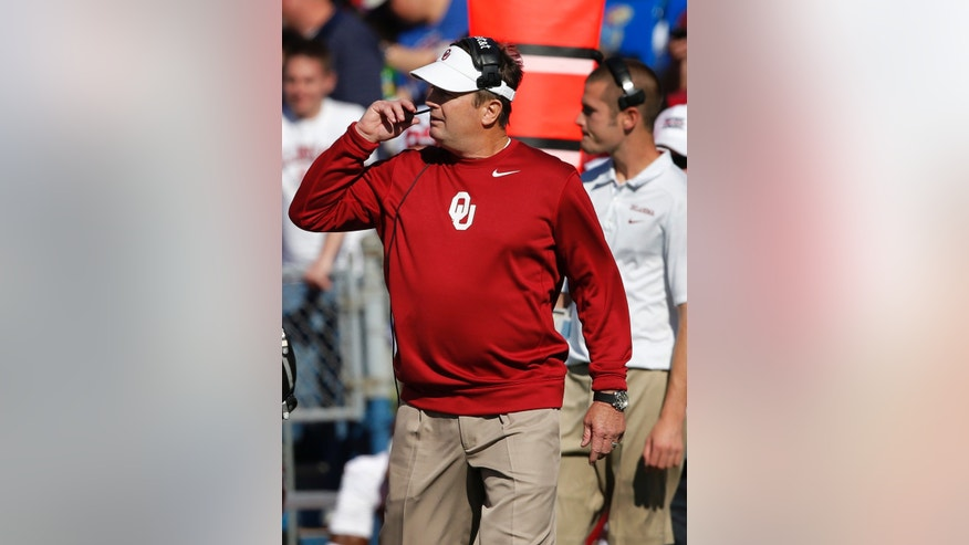 Oklahoma coach Bob Stoops walks on the sideline during the first half of an NCAA college football game against Kansas in Lawrence, Kan., Saturday, Oct. 19, 2013. (AP Photo/Orlin Wagner)