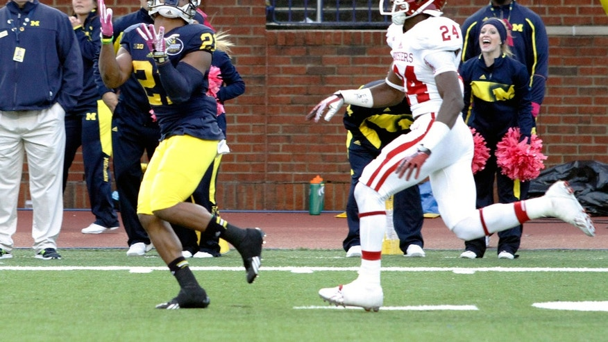 Michigan wide receiver Jeremy Gallon, left, catches a touchdown pass from quarterback Devin Gardner during the third quarter of Michigan's 63-47 win over Indiana during their NCAA football game at Michigan Stadium in Ann Arbor, Saturday, Oct. 19, 2013. (AP Photo/Lon Horwedel)