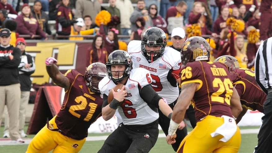 Northern Illinois quarterback Jordan Lynch gains yardage as CMU's Jeremy Gainer (21) and Shamari Benton (26) close in for a tackle during the third quarter of an NCAA college football game against Central Michigan in Mount Pleasant, Mich., Saturday, Oct. 19,2013  (AP Photo/John L. Russell)