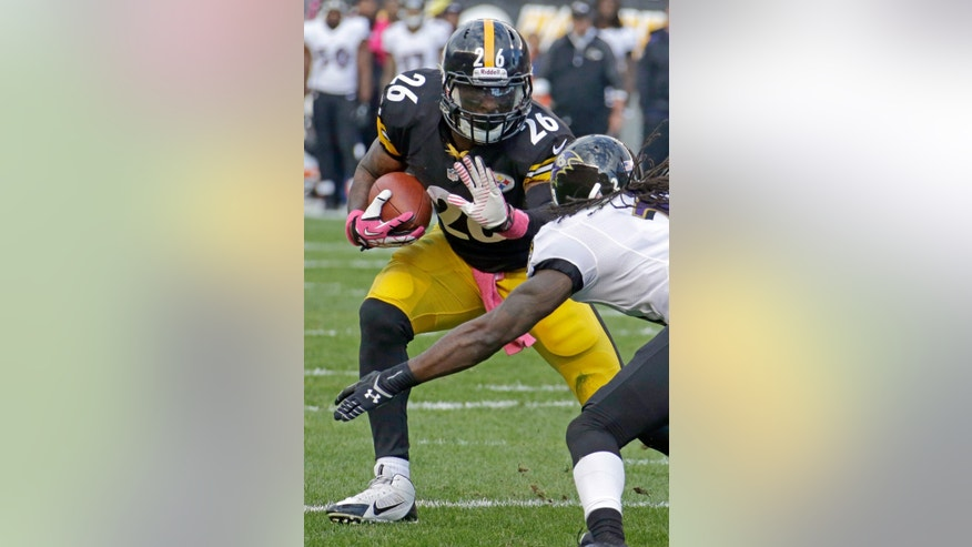 Pittsburgh Steelers running back Le'Veon Bell, left, runs the ball as Baltimore Ravens cornerback Lardarius Webb tries for the tackle in the first quarter of an NFL football game in Pittsburgh on Sunday, Oct. 20, 2013. (AP Photo/Gene J. Puskar)