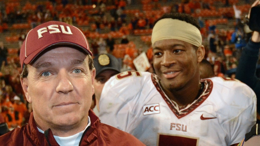 Florida State head coach Jimbo Fisher walks off the field with Florida State quarterback Jameis Winston (5) after the second half of an NCAA college football game against the Clemson, Sunday, Oct. 20, 2013, in Clemson, S.C. Florida State won 51-14. (AP Photo/Richard Shiro)