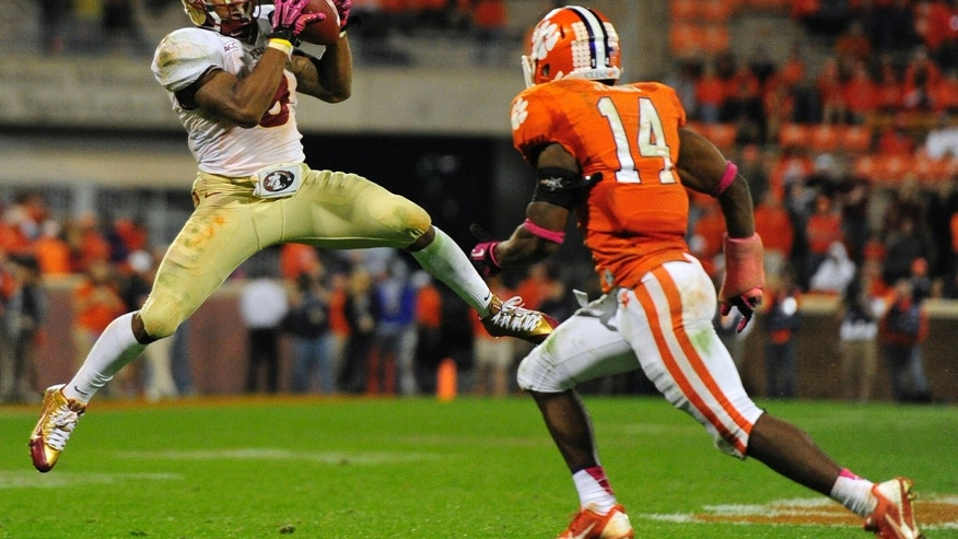 Florida State running back Devonta Freeman (8) makes the catch against Clemson defensive back Martin Jenkins (14) during the second half of an NCAA college football game, Saturday, Oct. 19, 2013, in Clemson, S.C. Florida State won 51-14. (AP Photo/Richard Shiro)