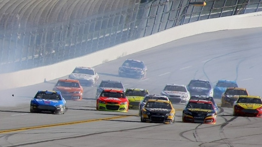 Sprint Cup Series driver Austin Dillon (14) goes airborne on the backstretch as Sprint Cup Series driver Jamie McMurray (1) leads cars on the final lap of the NASCAR Sprint Cup Series auto race at the Talladega Superspeedway in Talladega, Ala., Sunday, Oct. 20, 2013. McMurray won the race. (AP Photo/Greg McWilliams)