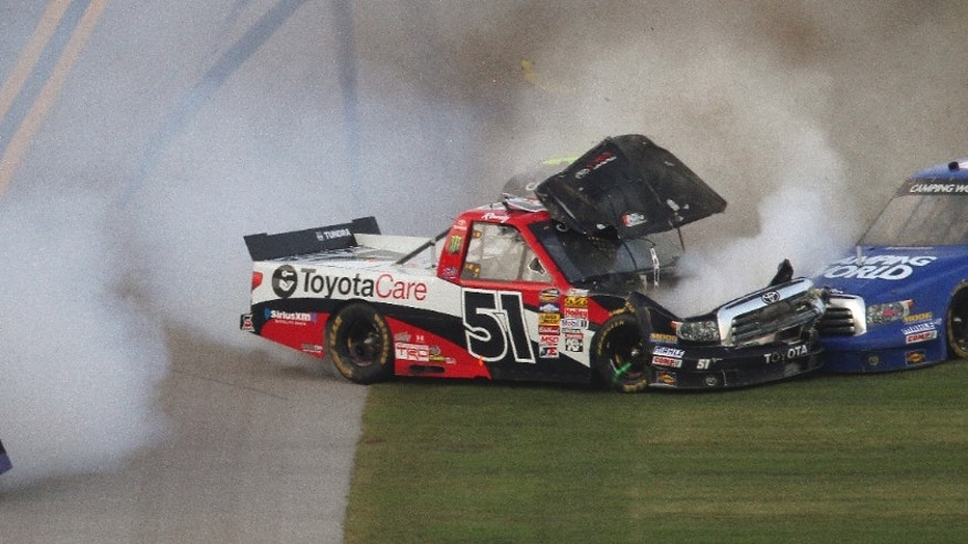 Miguel Paludo (32) tumbles down the front stretch as Kyle Busch (51) slams into Darrell Wallace Jr. (54) on the final lap of the NASCAR Trucks auto race at Talladega Superspeedway in Talladega, Ala., Saturday, Oct. 19, 2013. (AP Photo/Jay Alley)