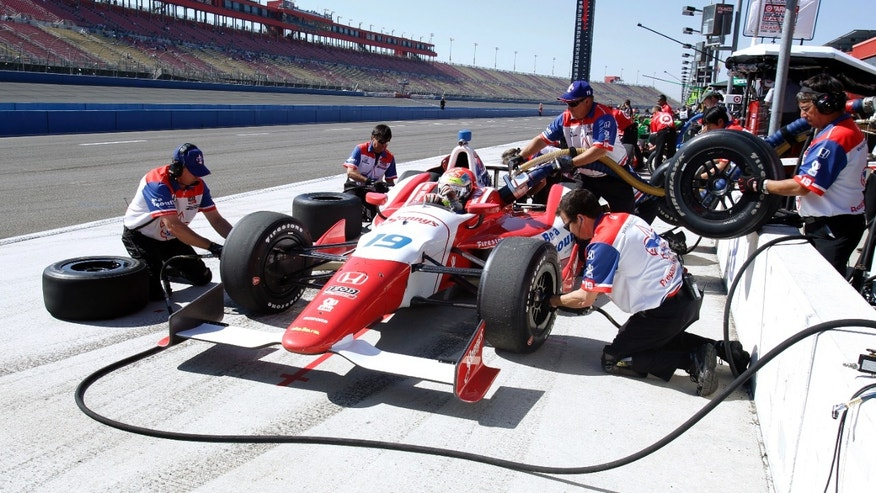 CORRECTS DAY OF RACE TO SATURDAY, INSTEAD OF SUNDAY - Justin Wilson, of England, gets new tires during a practice session for Saturday's IndyCar auto race at Auto Club Speedway, Friday, Oct. 18, 2013, in Fontana, Calif. (AP Photo/Alex Gallardo)