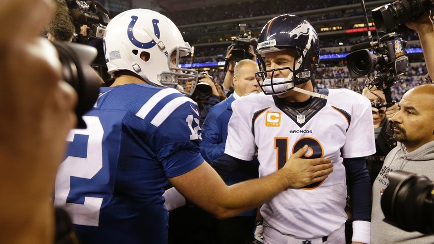 Denver Broncos quarterback Peyton Manning, right, greets Indianapolis Colts quarterback Andrew Luck (12) after an NFL football game, Sunday, Oct. 20, 2013, in Indianapolis. The Colts won 39-33. (AP Photo/Michael Conroy)