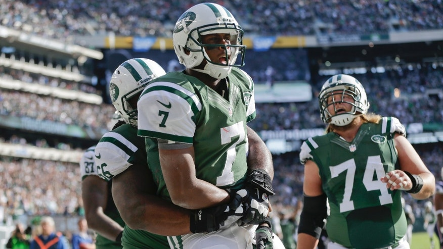 New York Jets quarterback Geno Smith (7) celebrates with New York Jets' Willie Colon (66) and Nick Mangold (74) after rushing for a touchdown during the second half of an NFL football game Sunday, Oct. 20, 2013 in East Rutherford, N.J.  (AP Photo/Seth Wenig)