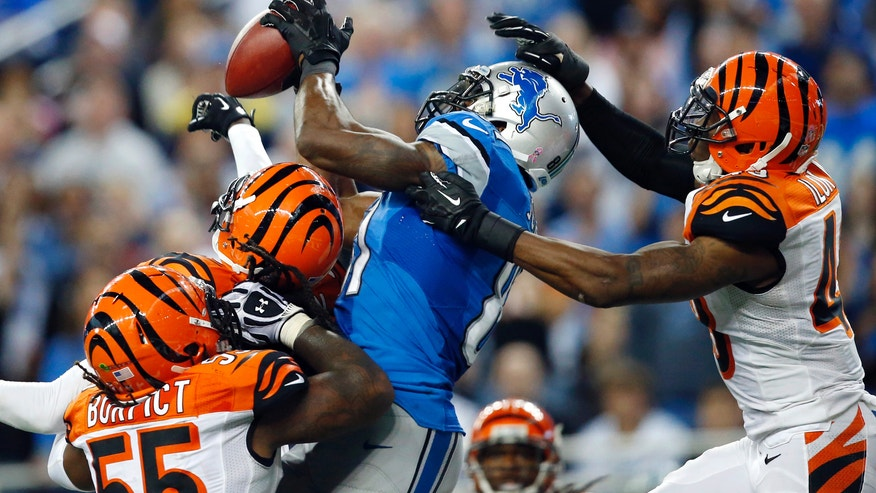 Detroit Lions wide receiver Calvin Johnson, second from right, catches a 50-yard touchdown reception over Cincinnati Bengals outside linebacker Vontaze Burfict, left, free safety Reggie Nelson, second from left, and strong safety George Iloka in the fourth quarter of an NFL football game Sunday, Oct. 20, 2013, in Detroit. (AP Photo/Rick Osentoski)