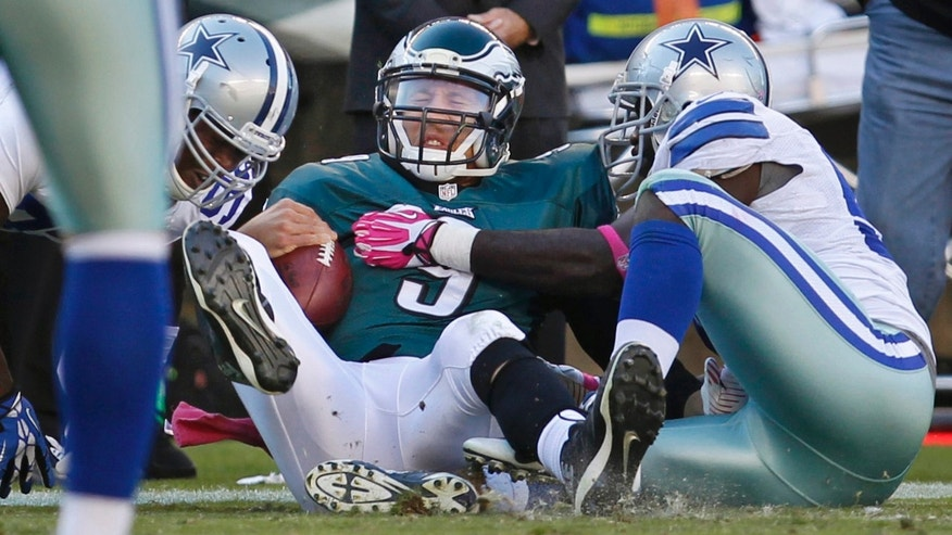 Philadelphia Eagles' quarterback Nick Foles, center, is sacked by the Dallas Cowboys' George Selvie, right, and another player in third quarter of an NFL football game on Sunday, Oct. 20, 2013, in Philadelphia. (AP Photo/Philadelphia Inquirer, Ron Cortes)  PHIX OUT; TV OUT; MAGS OUT; NEWARK OUT