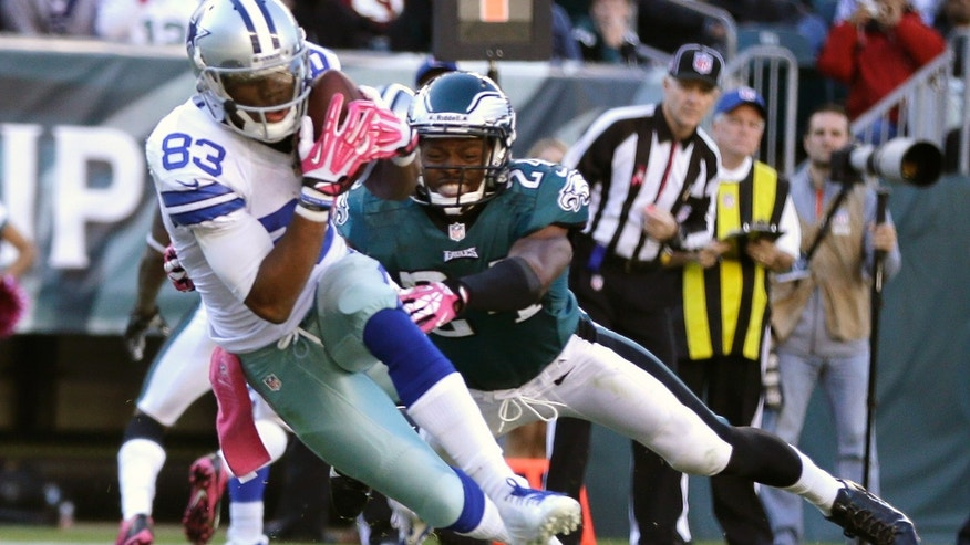 Dallas Cowboys' Terrance Williams (83) dives in for a touchdown on a pass from quarterback Tony Romo as Philadelphia Eagles cornerback Bradley Fletcher (24) defends on the play during the second half of an NFL football game, Sunday, Oct. 20, 2013, in Philadelphia. (AP Photo/Matt Rourke)