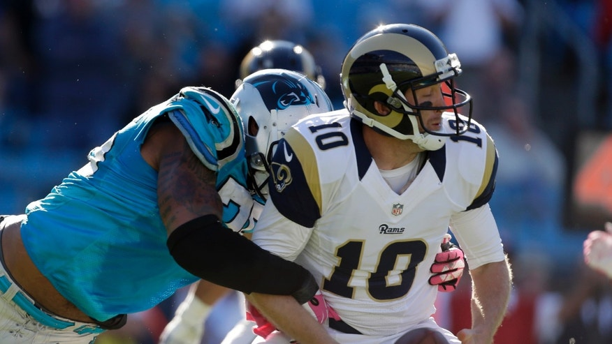 St. Louis Rams' Kellen Clemens, right, fumbles the ball after being hit by Carolina Panthers' Greg Hardy, left, in the second half of an NFL football game in Charlotte, N.C., Sunday, Oct. 20, 2013. The Panthers recovered the ball. The Panthers won 30-15. (AP Photo/Bob Leverone)