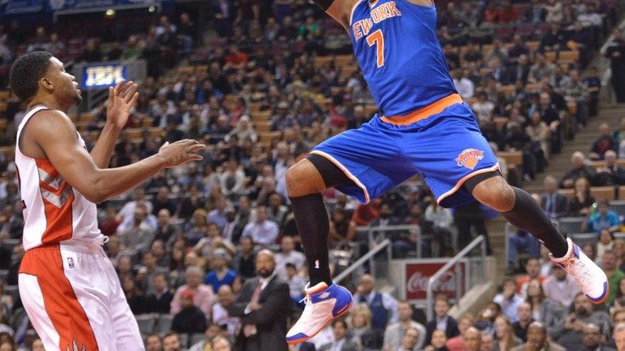 New York Knicks Carmelo Anthony (7) dunks the ball whileToronto Raptors Rudy Gay watches during first half NBA pre-season basketball action in Toronto on Tuesday, Oct. 21, 2013. (AP Photo/The Canadian Press, Nathan Denette)