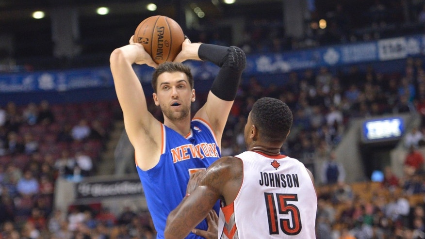 New York Knicks Andrea Bargnani passes the ball over Toronto Raptors Amir Johnson (15) during first half NBA pre-season basketball action in Toronto on Tuesday, Oct. 21, 2013. (AP Photo/The Canadian Press, Nathan Denette)