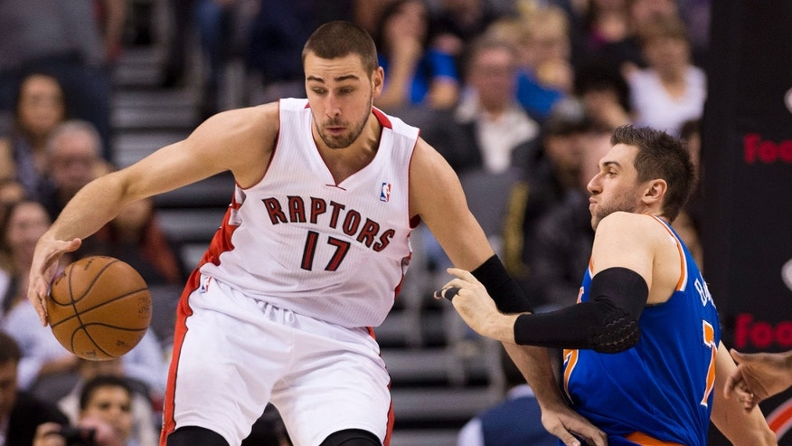 Toronto Raptors forward Jonas Valanciunas (17) knocks down New York Knicks forward Andrea Bargnani, right, during first half NBA pre-season basketball action in Toronto on Tuesday, Oct. 21, 2013. (AP Photo/The Canadian Press, Nathan Denette)