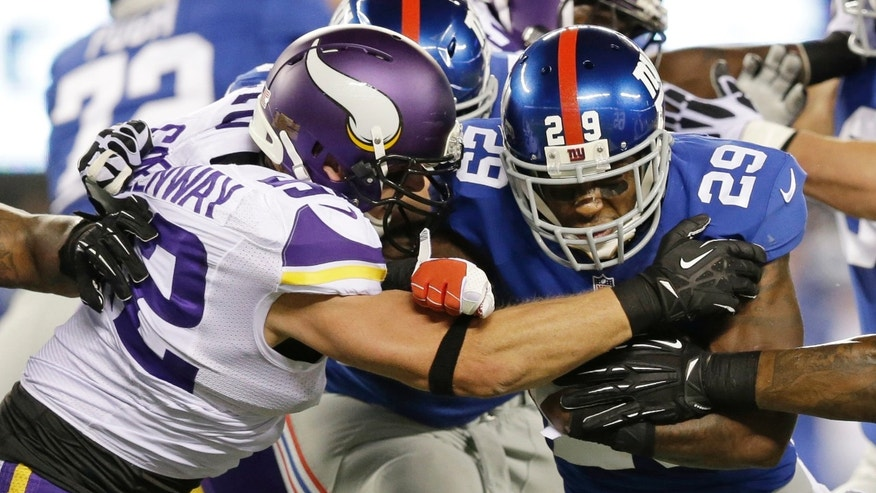 Minnesota Vikings outside linebacker Chad Greenway, left, tackles New York Giants running back Michael Cox (29) during the first half of an NFL football game Monday, Oct. 21, 2013 in East Rutherford, N.J. (AP Photo/Julio Cortez)