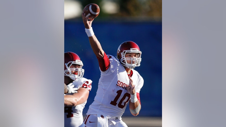 Oklahoma quarterback Blake Bell (10) passes to a teammate during the second half of an NCAA college football game against Kansas in Lawrence, Kan., Saturday, Oct. 19, 2013. Oklahoma defeated Kansas 34-19. (AP Photo/Orlin Wagner)