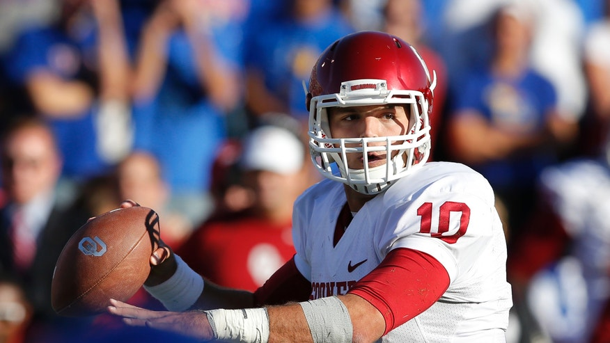 Oklahoma quarterback Blake Bell (10) passes to a teammate during the second half of an NCAA college football game against Kansas in Lawrence, Kan., Saturday, Oct. 19, 2013. Bell passed for 131 yards and two touchdowns. Oklahoma defeated Kansas 34-19. (AP Photo/Orlin Wagner)