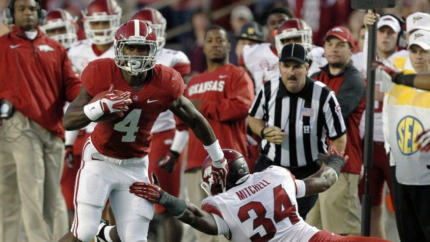 Alabama running back T.J. Yeldon (4) gets around Arkansas linebacker Braylon Mitchell (34) and picks up a first down during the first half of an NCAA college football game on Saturday, Oct. 19, 2013, in Tuscaloosa, Ala. (AP Photo/Butch Dill)