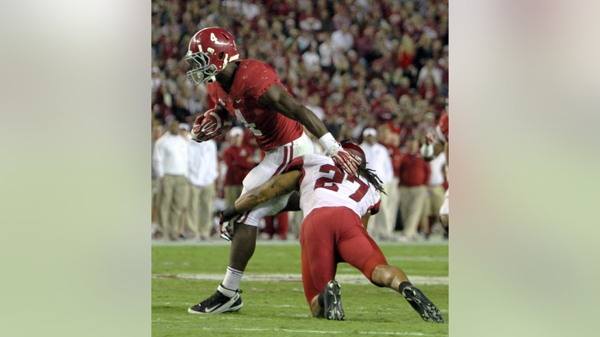Alabama running back T.J. Yeldon (4) breaks the tackle of Arkansas safety Alan Turner (27) and runs for a touchdown during the second half of an NCAA college football game on Saturday, Oct. 19, 2013, in Tuscaloosa, Ala. (AP Photo/Butch Dill)