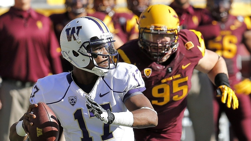 Washington quarterback Keith Price (17) throws as Arizona State defensive end Gannon Conway (95) defends during the first half of an NCAA college football game, Saturday, Oct. 19, 2013, in Tempe, Ariz. (AP Photo/Matt York)
