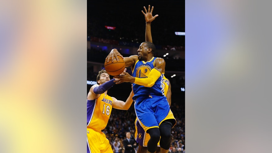 Andre Iguodala of Golden State Warriors, top, dives against Pau Gasol of Los Angeles Lakers, left, during a 2013-2014 NBA preseason game between Lakers and Warriors at Mercedes-Benz Arena in  Shanghai, China, Friday, Oct. 18, 2013. (AP Photo/Eugene Hoshiko)