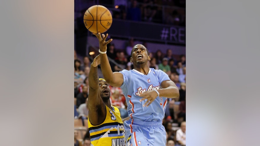 The Los Angeles Clippers' Chris Paul, right, shoots over the Denver Nuggets' Ty Lawson during the first half of a preseason NBA basketball game on Saturday, Oct. 19, 2013, in Las Vegas. The Clippers defeated the Nuggets in overtime 118-111. (AP Photo/Isaac Brekken)