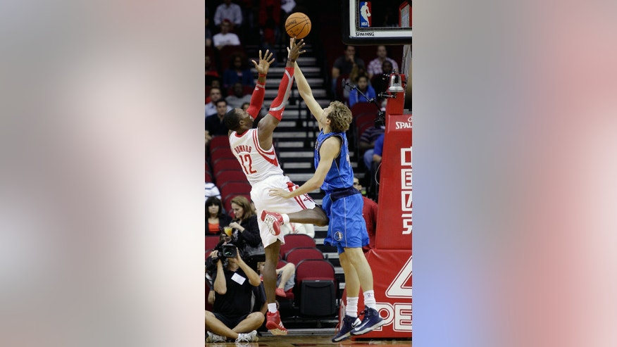 Houston Rocket's Dwight Howard, left, shoots a fade away over Dallas Maverick's Dirk Nowitzki, right, in the first half of a preseason NBA basketball game Monday, Oct. 21, 2013, in Houston. Houston won 100-95. (AP Photo/Bob Levey)