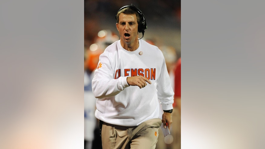 Clemson coach Dabo Swinney runs down the sidelines during the first half of an NCAA college football game against Florida State, Saturday, Oct. 19, 2013, in Clemson, S.C. (AP Photo/Richard Shiro)