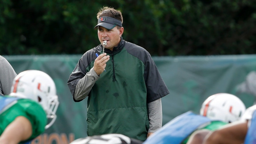 Miami head coach Al Golden, rear, watches a drill during team practice, Tuesday, Oct. 22, 2013, in Coral Gables, Fla. Miami's football team will lose nine scholarships and the men's basketball team will lose three, as part of the penalties the school was handed Tuesday by the NCAA as the Nevin Shapiro scandal presumably drew to a close. (AP Photo/Wilfredo Lee)