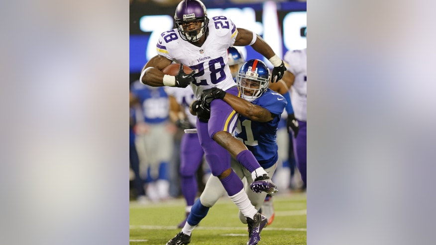 Minnesota Vikings running back Adrian Peterson (28) is tackled by New York Giants' Ryan Mundy (21) during the second half of an NFL football game Monday, Oct. 21, 2013 in East Rutherford, N.J. (AP Photo/Julio Cortez)