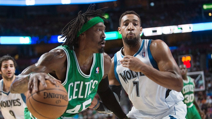 Boston Celtics' Gerald Wallace, left, drives to the net as Minnesota Timberwolves' Derrick Williams defends during the second quarter of an NBA preseason basketball game in Montreal, Sunday, Oct. 20, 2013. (AP Photo/The Canadian Press, Graham Hughes)