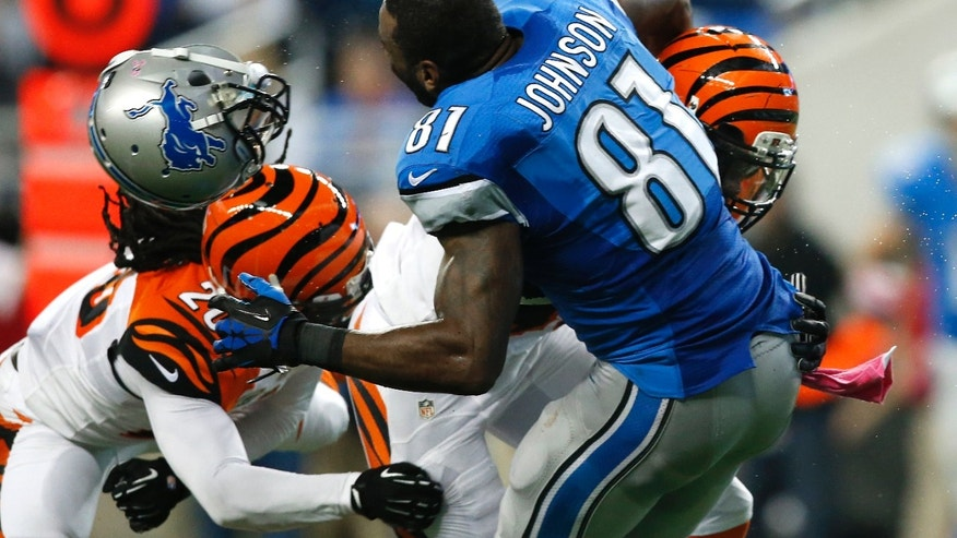 Detroit Lions wide receiver Calvin Johnson (81) loses his helmet trying to catch a pass while being hit by Cincinnati Bengals strong safety George Iloka (43)  as safety Reggie Nelson (20) moves in to help in the second quarter of an NFL football game against Sunday, Oct. 20, 2013, in Detroit. (AP Photo/Rick Osentoski)