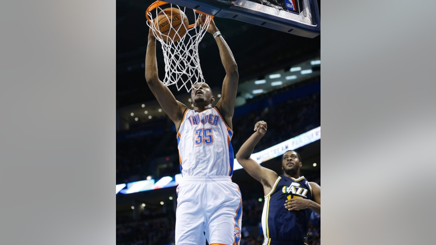 Oklahoma City Thunder forward Kevin Durant (35) dunks in front of Utah Jazz forward Derrick Favors (15) in the first quarter of a preseason NBA basketball game in Oklahoma City, Sunday, Oct. 20, 2013. (AP Photo/Sue Ogrocki)