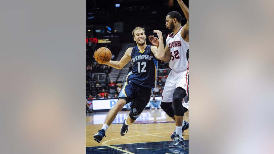 Memphis Grizzlies' Nick Calathes (12) drives against the defense of Atlanta Hawks forward Mike Scott (32) during the second half of an NBA preseason basketball game, Sunday, Oct. 20, 2013, in Atlanta. (AP Photo/ John Amis)