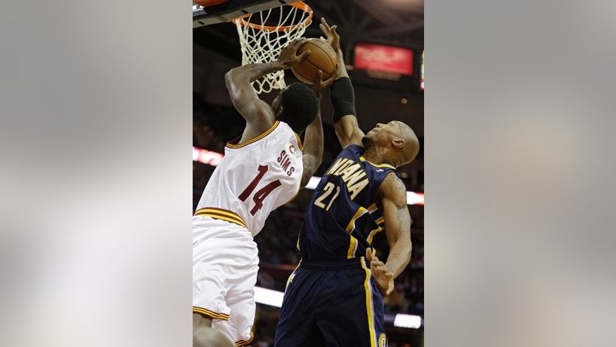 Indiana Pacers' David West (21) blocks a shot by Cleveland Cavaliers' Henry Sims (14) in the first quarter of a preseason NBA basketball game Saturday, Oct. 19, 2013, in Cleveland. (AP Photo/Mark Duncan)