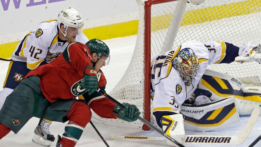 Nashville Predators goalie Pekka Rinne, right, of Finland stops a shot by Minnesota Wild's Zach Parise, left, as Mattias Ekholm of Sweden tries to break up the scoring attempt in the first period of an NHL hockey game, Tuesday, Oct. 22, 2013, in St. Paul, Minn. (AP Photo/Jim Mone)
