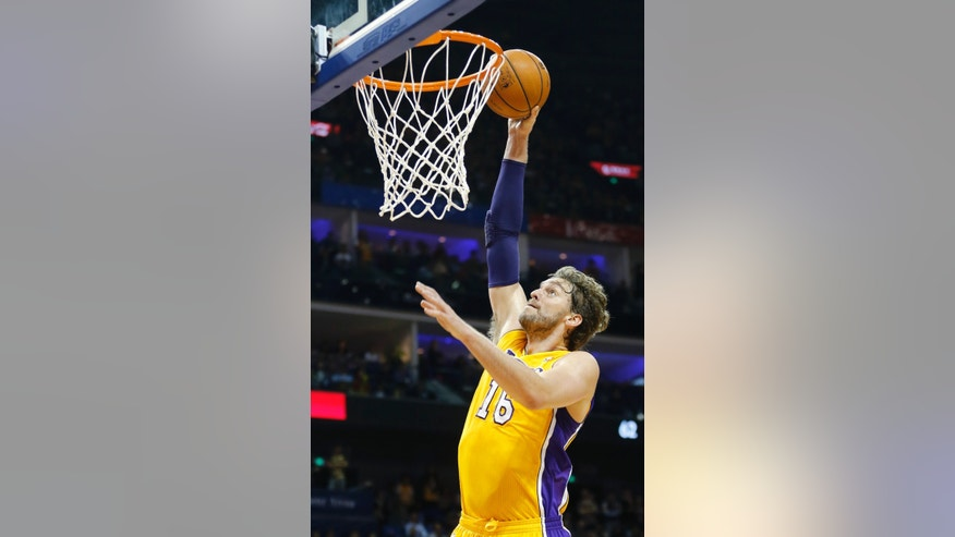 Pau Gasol of Los Angeles Lakers scores against Golden State Warriors during a 2013-2014 NBA preseason game between Lakers and Warriors at Mercedes-Benz Arena in  Shanghai, China, Friday, Oct. 18, 2013. (AP Photo/Eugene Hoshiko)