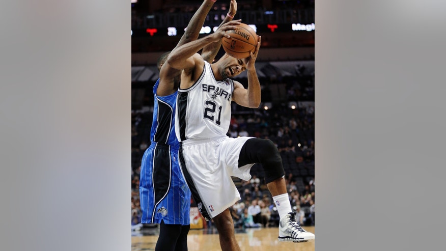 San Antonio Spurs' Tim Duncan (21) reacts as he fouled by Orlando Magic's Kyle O'Quinn, left, during the first half of a preseason NBA basketball game, Tuesday, Oct. 22, 2013, in San Antonio. (AP Photo/Eric Gay)