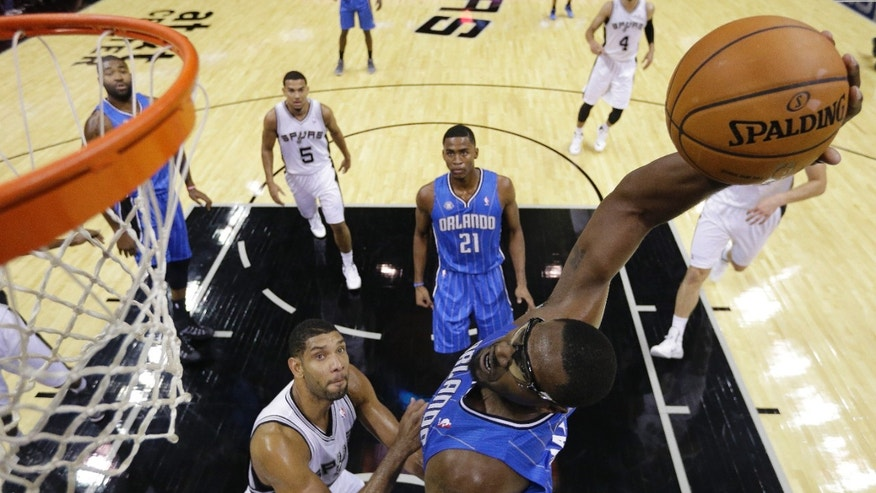 Orlando Magic's Jason Maxiell, right, dunks the ball over San Antonio Spurs' Tim Duncan, left, during the first half of a preseason NBA basketball game, Tuesday, Oct. 22, 2013, in San Antonio. (AP Photo/Eric Gay)