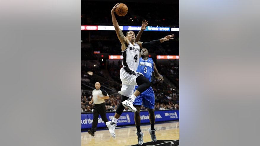San Antonio Spurs' Danny Green (4) drives past Orlando Magic's Victor Oladipo to score during the first half of a preseason NBA basketball game, Tuesday, Oct. 22, 2013, in San Antonio. (AP Photo/Eric Gay)