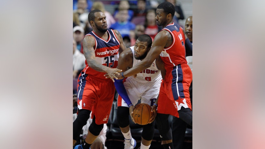 Detroit Pistons center Greg Monroe, center, is trapped in a corner by Washington Wizards forward Trevor Booker (35) and guard John Wall during the first half of a preseason NBA basketball game Tuesday, Oct. 22, 2013, in Auburn Hills, Mich. (AP Photo/Duane Burleson)