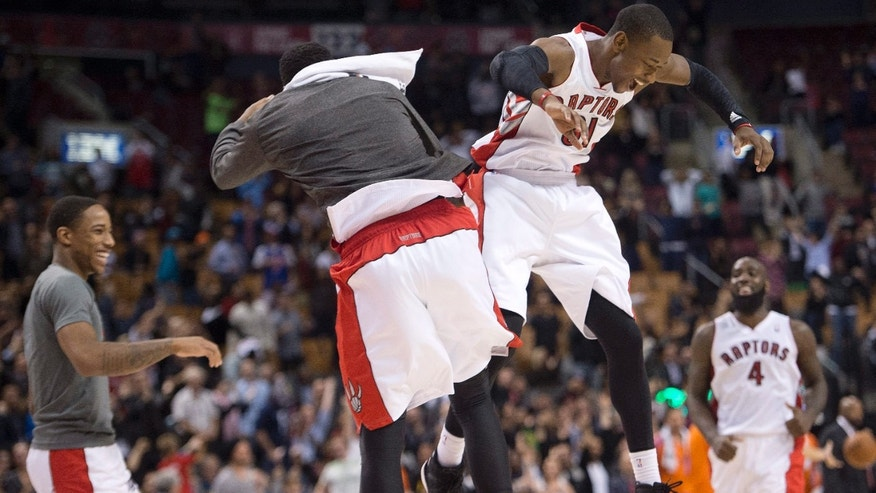 Toronto Raptors forward Terrence Ross, right, celebrates his tying three-point shot at the buzzer with Raptors forward Rudy Gay, left, while playing against the New York Knicks during over-time NBA pre-season basketball action in Toronto on Tuesday, Oct. 21, 2013. (AP Photo/The Canadian Press, Nathan Denette)