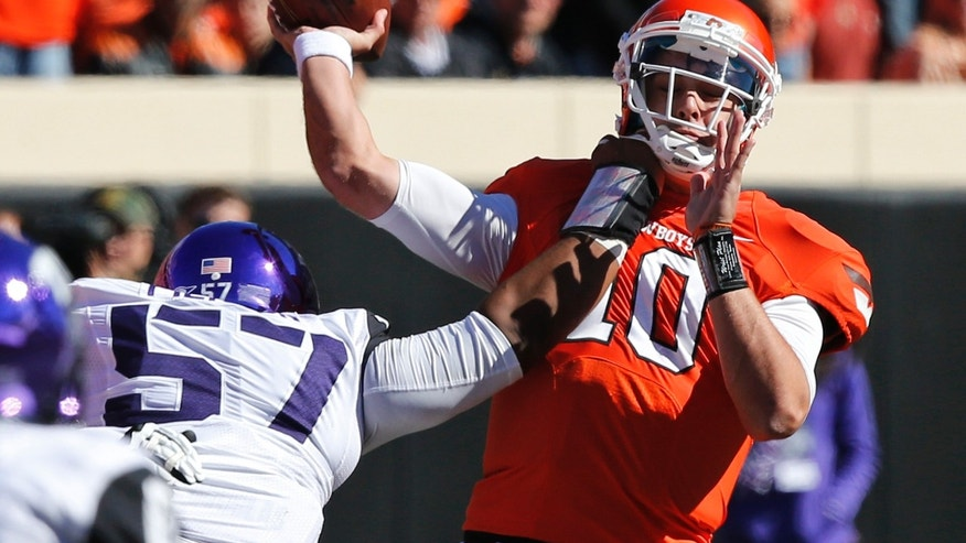 Oklahoma State quarterback Clint Chelf (10) passes under pressure from TCU defender Davion Pierson (57) in the second quarter of an NCAA college football game in Stillwater, Okla., Saturday, Oct. 19, 2013. Oklahoma State won 24-10. (AP Photo/Sue Ogrocki)