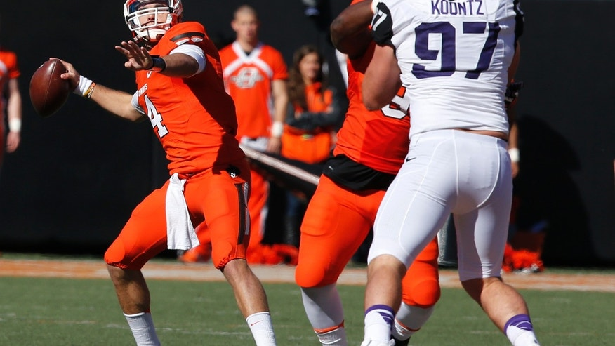 Oklahoma State quarterback J.W. Walsh (4) passes under pressure from TCU defender Jon Koontz (97) in the first quarter of an NCAA college football game in Stillwater, Okla., Saturday, Oct. 19, 2013. Oklahoma State won 24-10. (AP Photo/Sue Ogrocki)