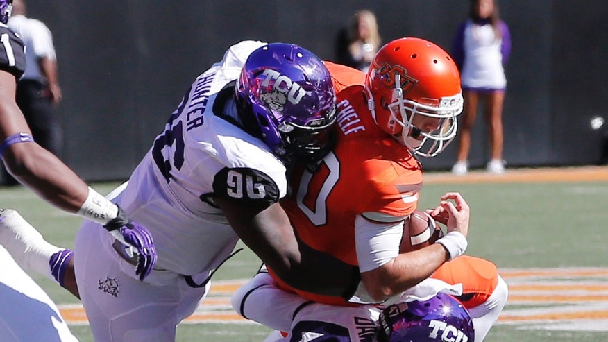 Oklahoma State quarterback Clint Chelf (10) is tackled by TCU's Chucky Hunter (96) and Paul Dawson (47) in the second quarter of an NCAA college football game in Stillwater, Okla., Saturday, Oct. 19, 2013. Oklahoma State won 24-10. (AP Photo/Sue Ogrocki)